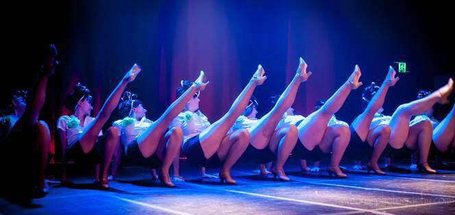 Row of burlesque dancers with legs in the air on stage