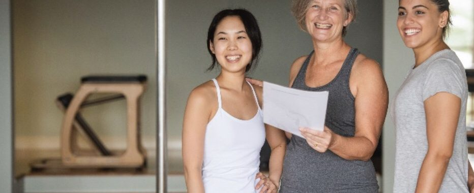 Staff from Movement Principle Pilates Paddington studio smiling and checking notes