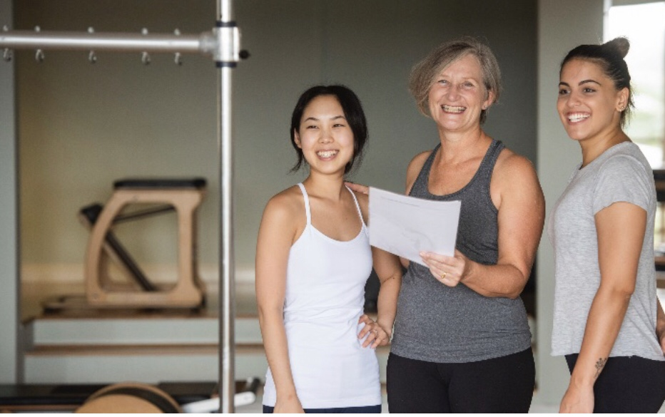 Staff from Movement Principle Pilates Paddington studio smiling and checking notes