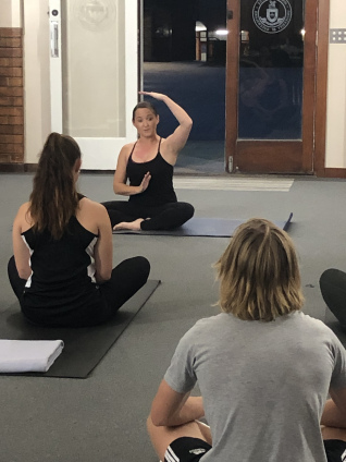 Pilates instructor sitting at front of class teaching