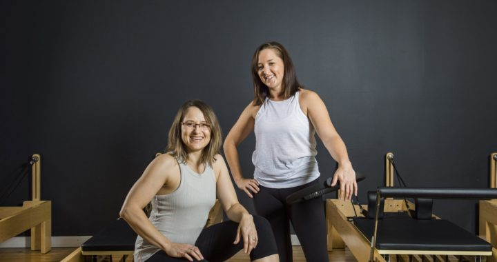 Cat and Anita from Movement Principle Pilates Brisbane smiling with reformer pilates equipment