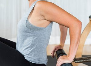 Woman using reformer pilates equipment