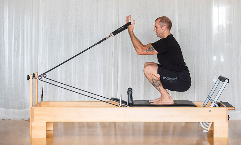 Edwin from Movement Principle Pilates Brisbane in squatting pose on reformer pilates machine