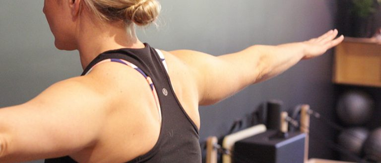 Blonde woman in sports singlet holding arms straight out at shoulder height in pilates studio