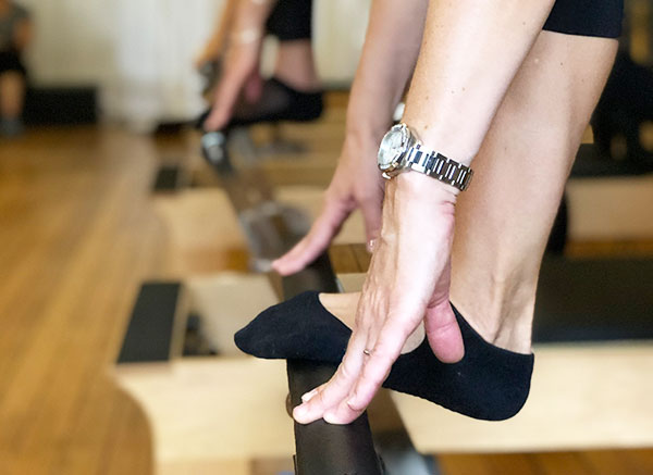 Hands with silver watch reaching reformer pilates bar with foot in black sock on it