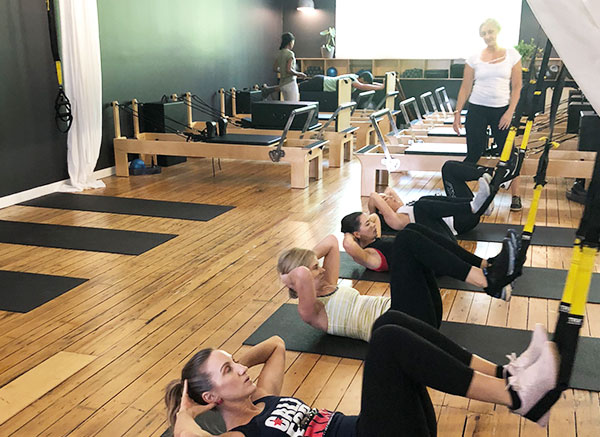 Women in pilates mat class doing crunches with instructor standing at back