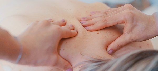 Hands massaging bare back of person with grey hair