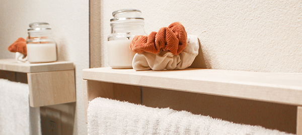 Jar candle and hair scrunchies on towel rack nest to mirror