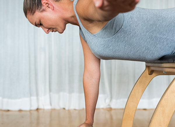 Pilates instructor in grey singlet balanced on wooden chair facing downwards