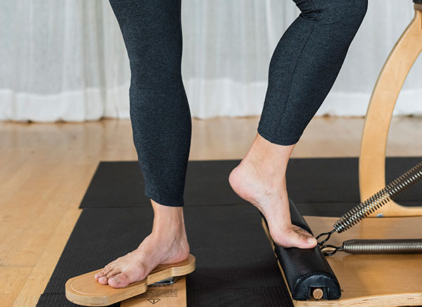 Women's legs and feet posed on foot-specific pilates equipment