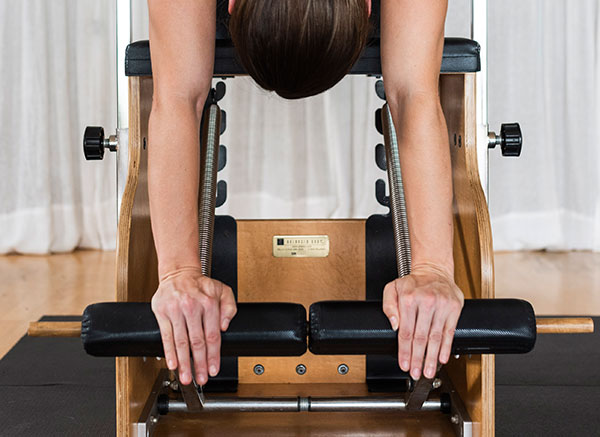 Back of woman's head upside down on pilates wunda chair with hands on foot pedals