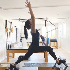 young woman wearing black gym clothes in pilates studio lunging on reformer machine with arms stretched up