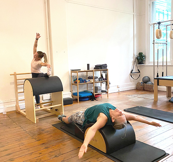 Two women stretching on equipment in Pilates studio with wooden floors