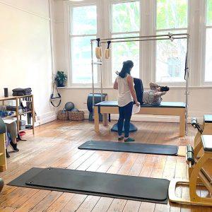 Women instructing man on equipment in Pilates studio with wooden floors and big windows