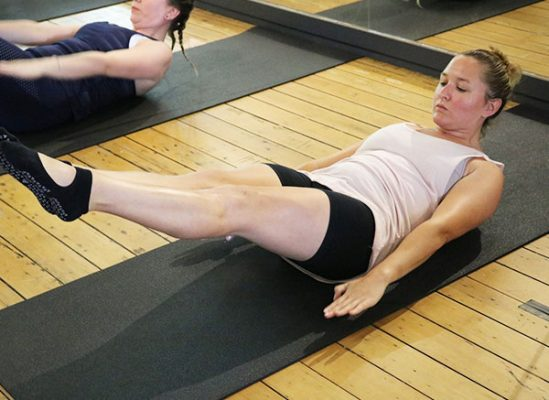 Two woman holding pilates pose on mats on wooden floor